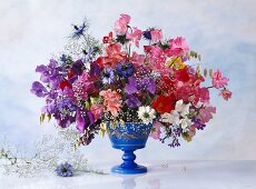 Colourful spring bouquet in blue vase against light, mottled wall