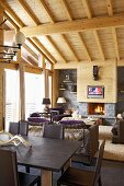 Open-plan living-dining room with cosy open fire in wooden house