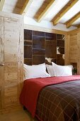 Modern bedroom with rustic wooden wardrobe and panels of animal skin on wall
