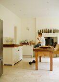 Boy sitting on wooden table in plain kitchen
