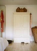 Wicker baskets on white-painted rustic wardrobe in plain bedroom