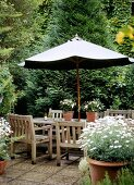 Dining area on terrace with wooden chairs beneath parasol