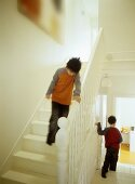Children on white-painted, wooden staircase with turned balusters