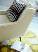 Cushion on armchair upholstered in white leather next to open book and mug on rug