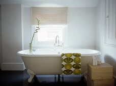 Free-standing, vintage bathtub with retro-patterned towel draped over rim