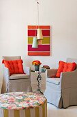 View over pouffe of orange cushions on armchairs with grey loose covers in front of wall with modern artwork and fifties pendant ceiling lamps