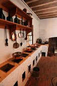 Rustic kitchen with multiple hearths in masonry counter and copper kitchen utensils