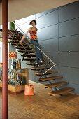 Teenager sliding down banister of modern staircase