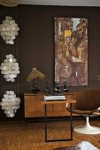 Desk and shell chair with brown cover against wall painted dark brown