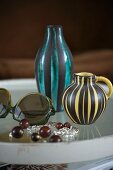 Tray with two different striped vases and sunglasses