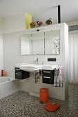 Sink and mirror on white tiled partition in bathroom with terrazzo floor