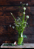 White onion and coriander flowers in preserving jar against rustic wooden wall