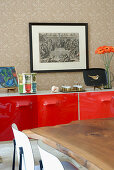 Detail of solid wooden table in front of sideboard with red lacquer doors