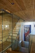 Staircase with glass partition wall in wooden house