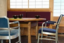 Teeschalen auf Esstisch aus Holz und gepolsterte Stühle mit Metallgestell