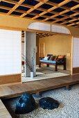 Vorraum mit Podest und Kiesboden vor offenem Wohnraum in japanischem Stil