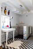Black and white floor tiles and old Delft tiles in the bathroom of a country house with exotic masks hung above a retro, free-standing wash stand