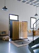 Künstlerisch gestalteter Windfang aus Holzstäben vor Haustür in loftartigem Wohnraum