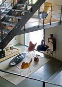 Blick von Galerie in minimalistischen Wohnraum auf Klassiker Sesseln und Couchtisch