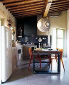 Blaugeflieste Küche mit rustikaler Küchenzeile und bunter Vintage Essgruppe unter moderner Hängeleuchte