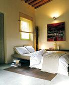 Schlafzimmer mit Betonestrich und Holzdielenboden; an der Wand ein modernes Gemälde und warmes Licht einer Wandleuchte