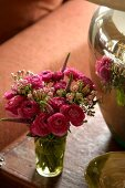 A bouquet of ranunculus reflected in a silver vase