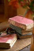 Antique, tattered books on a wooden surface and a pair of modern reading glasses