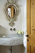 Playful, antique style mirror above a modern sink made of hewn stone