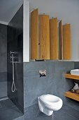 Rotatable wooden screen panels in modern bathroom with slate tiles