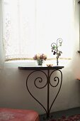 Small, old console table with metal legs in stylized heart form under a window with a romantic retro curtain