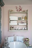Old fashioned bathroom with a playful 'Shabby Style' with shelves above a bathtub