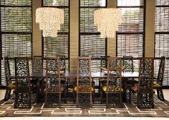 Striking chairs with pierced backs at a long table with modern chandeliers
