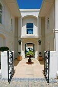 Sunny entrance with wrought iron gate, terra cotta tiles and small trees in square wooden planters