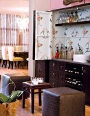 View of dining area beyond vintage-style drinks cabinet with upholstered cube stools