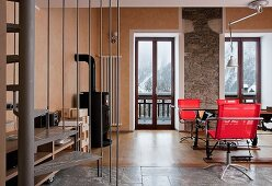 Comfortable interior in chalet with rustic stone wall, wood-burning stove, glass dining table and red swivel chairs