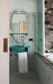 Bathroom with glass sink and oval mirror; sliding window opens to reveal an outdoor bathtub