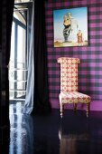 Chair with patterned upholstery fabric in front of a purple plaid wall with a modern painting
