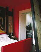 Bed with red bedstead in red-painted bedroom with ensuite bathroom