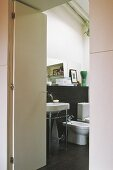 View of washstand and bathroom fittings through open door
