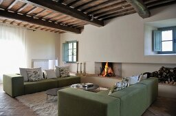 Cubist sofas in front of open fire in renovated country house