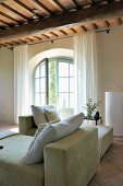 Cushions on chaise longue in front of arched terrace door in renovated country house