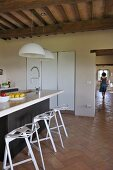 Kitchen island with bar stools in open-plan kitchen and view of woman in corridor