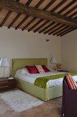 Modern bedroom below rustic ceiling in renovated country house