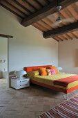 Purist bedroom with designer bed on old terracotta floor below rustic ceiling