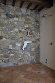 Shower head with running water in floor-level shower with stone wall