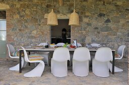 Mediterranean terrace dining area with white shell chairs and table against stone wall