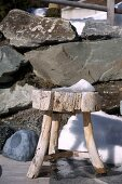 Rustic wooden footstool in front of boulders and a small snow shovel