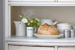 Bread in dish amongst crockery on dresser surface