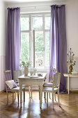 Old French chairs around wooden table in Gustavian style next to window with floor-length purple curtains
