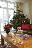 Bouquet of roses, tealight holders and presents on coffee table; decorated Christmas tree in front of window